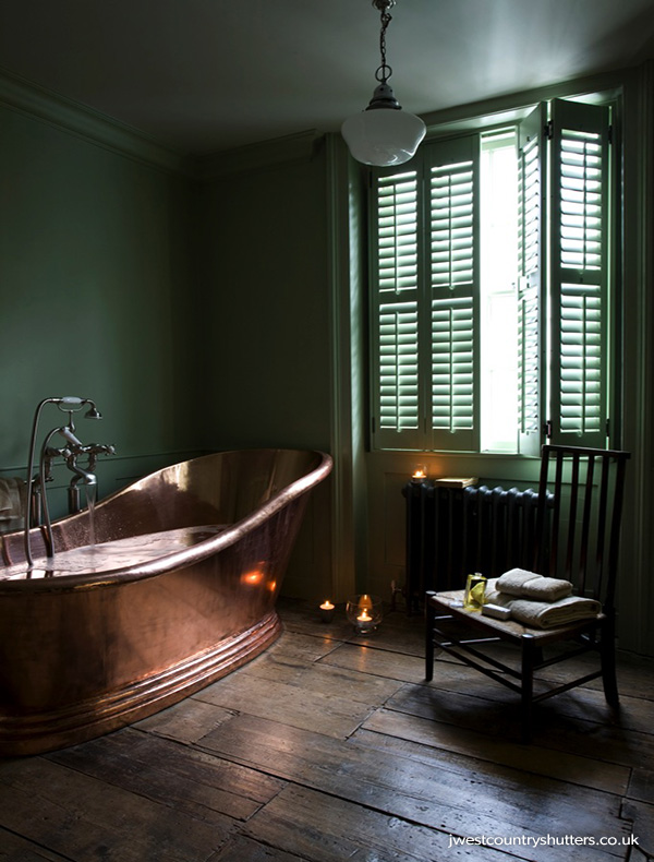 Green bathroom with large copper bath